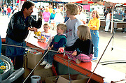 Carnival pitchman and mom with 3, 5 and 6 yr olds at MN State Fair.  St Paul Minnesota USA