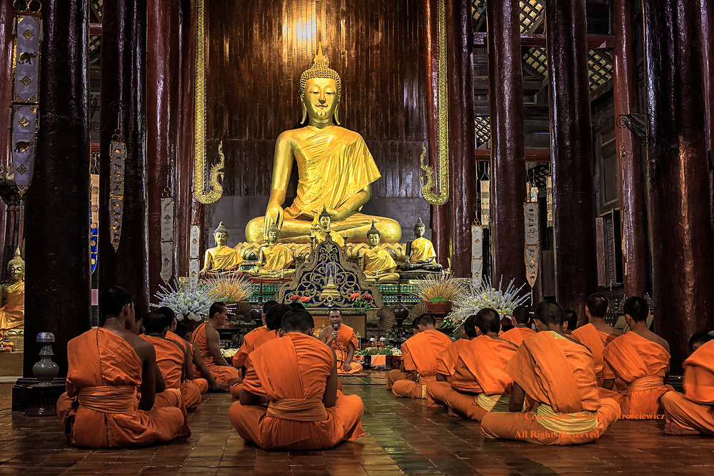 Evening Prayers: The senior Buddhist monk sits in front of numerous golden statues of the Buddha and before rows of disciple, leading evening prayers in the main temple of Wat Pantao, Chiang Mai Thailand.