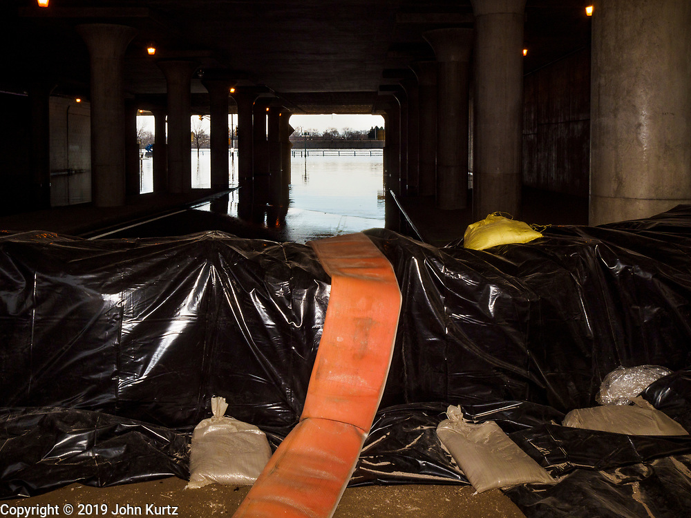 29 MARCH 2019 - ST. PAUL, MN: The end of Sibley St. in St. Paul is closed by Mississippi River floodwaters with pump hoses pre-positioned for use if flooding gets worse. The Mississippi River through the Twin Cities has already hit flood stage. Several roads and parks in St Paul are already closed in anticipation of higher flood levels. Weather forecasters and hydrologists have backed off a little on earlier predictions of severe flooding because the snow melt has been slower than expected.    PHOTO BY JACK KURTZ