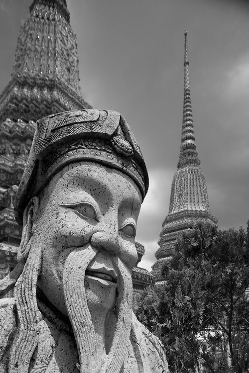 Asia, Thailand, Bangkok, Intricately carved royal statue on grounds of Wat Po Buddhist Temple surrounding by spires