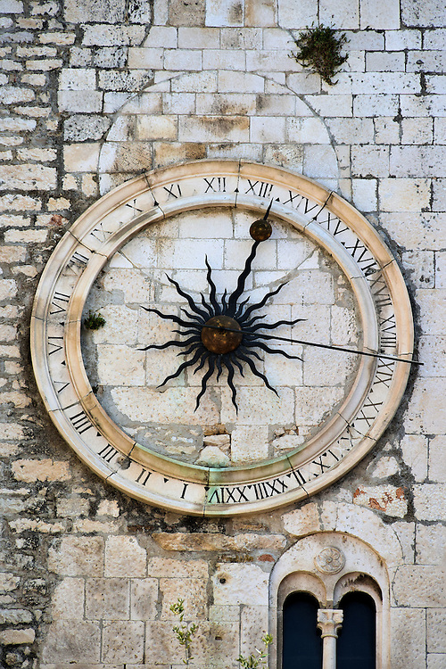 Church of Our Lady Bell Tower at Diocletian&rsquo;s Palace in Split, Croatia <br /> Next to the Iron Gate, which is also called Porta Ferrea, is this unique clock with 24 Roman numerals. The Tower Clock was added next to Crkva Gospa od Zvonik or the Church of Our Lady of the Bell Tower during the 11th century. It is best seen from Pjaca Square along the western outside wall of Diocletian&rsquo;s Palace. The chapel was founded in the 6th century.