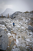 Woman walking up a trail in a snow squall, Enchantment Lakes Wilderness Area, Washington Cascades, USA.