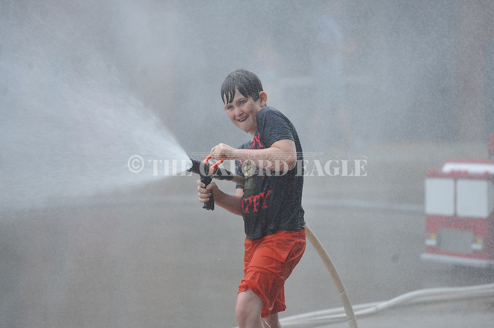 Hunter Tidwell uses a miniature hose to squirt water at others during a kids fire camp at Fire Station No. 4 in Oxford, Miss. on Friday, June 27, 2014. (AP Photo/Oxford Eagle, Bruce Newman)