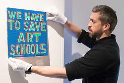 Christies, St James, London, March 4th 2016. A gallery technician hangs an artwork pleading the case for art in schools at the preview for the It's Our World charity auction at Christie's. Over 40 leading artists including David Hockney, Sir Antony Gormley, David Nash, Sir Peter Blake, Yinka Shonibare, Sir Quentin Blake, Emily Young and Maggi Hambling have committed artworks to the It's Our World Auction in support of The Big Draw and Jupiter Artland Foundation, to be sold at Christie's London on 10 March 2016.<br />  ///FOR LICENCING CONTACT: paul@pauldaveycreative.co.uk TEL:+44 (0) 7966 016 296 or +44 (0) 20 8969 6875. ©2015 Paul R Davey. All rights reserved.