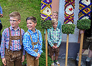 "Younger boys will take turns carrying the ""junior"" prangstangen. These poles are shorter but hefty enough to demand strength, balance, and concentration."