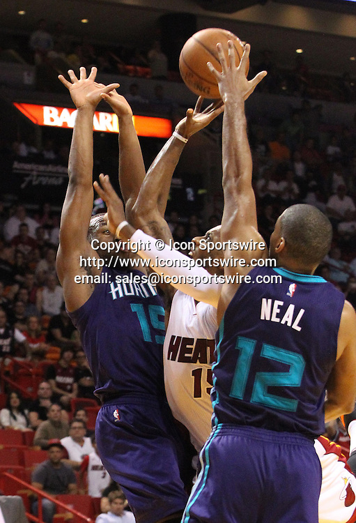 Nov. 23, 2014 - Miami, FL, USA - Miami Heat's Mario Chalmers goes to the hoop between the defense of Charlotte Hornets' Kemba Walker and Gary Neal during the fourth quarter on Sunday, Nov. 23, 2014, at AmericanAirlines Arena in Miami.