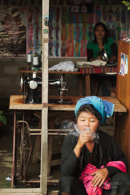 Minority woman smoking outside sewing shop at Nyaungshwe