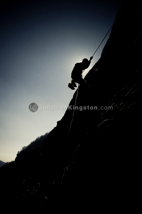 Silhouette of a young man rappelling down a cliff face on Whitesides Mountain, Cashiers Valley, North Carolina. Whitesides is known for its south facing warm walls that are climbable in the winter time as well as for its frightening, sparsely protected climbing leads.(releasecode: jk_mr1010) (Model Released)
