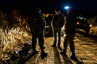 A suspected rhino poacher lies facedown and handcuffed after a successful intelligence-led operation to apprehend the poaching gang.