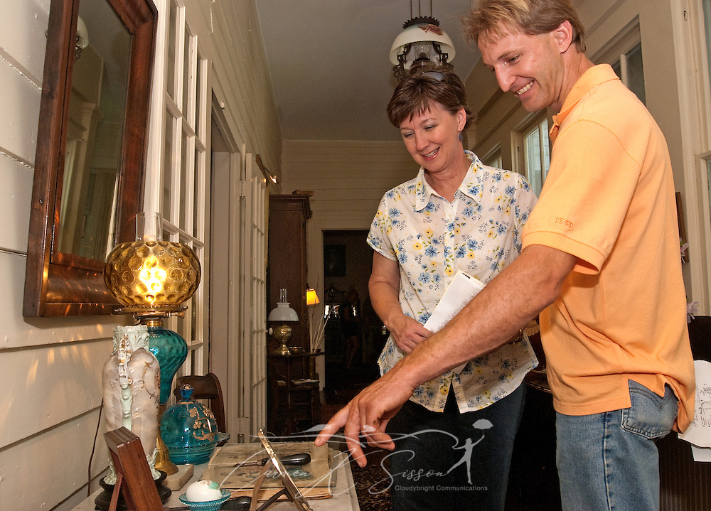 Beth Ballinger and Heath Wallace look at an 1873 Peterson Magazine at the Amzi Love Home in Columbus, Miss. April 17, 2010. The 1848 home, which has been featured in Fodor's Travel Guide and The New York Times Travel Magazine, was among nearly two dozen on tour during Columbus' annual Spring Pilgrimage. (Photo by Carmen K. Sisson/Cloudybright)