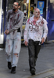 "© Licensed to London News Pictures. 15/09/2013<br /> Cigarette break for two zombies.<br /> Brentwood zombie movie ""Welcome to Essex""<br /> The final shoot of  Welcome to Essex  has seen 1500 zombies running down Brentwood High Street this morning (15.09.2013) on the last day of filming for one of the biggest low-budget horror films.<br /> The film follows  Ryley Dunn played by Catherine Delaloye who after a drunken fall that lands her unconscious wakes up to find Brentwood over run with Zombies...<br /> Photo credit :Grant Falvey/LNP"