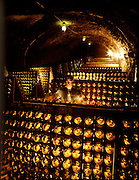 "Calistoga, California.Ramon Viera gently knocks or ""riddles"" the collected sediment which has settled in the necks of the countless wine bottles in the Schramsberg wine cave, one of the oldest in Napa Valley, California. Though it is a tedious process, riddling is a fundamental step in the time consuming production of sparkling wine."