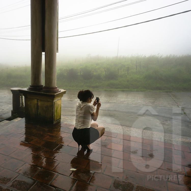 A woman squats on the ground to shoot a photo of a misty scene with a camera phone, Mau Son, Lang Son Province, Vietnam, Southeast Asia