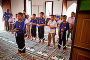 "Sept. 24, 2009 -- PATTANI, THAILAND: Thai schoolboys pray in the Krue Se Mosque in Pattani, Thailand. The Krue Se Mosque is one of Thailand's most historic mosques and long a flash point in Muslim - Buddhist confrontation. The mosque was first destroyed by advancing Thais when Pattani was an independent kingdom in 1786. It was restored in the 1980's but heavily damaged by rockets fired by unknown assailants in 2005. It has since been partially restored by local Muslims and the Thai government. Thailand's three southern most provinces; Yala, Pattani and Narathiwat are often called ""restive"" and a decades long Muslim insurgency has gained traction recently and nearly 4,000 people have been killed since 2004. The three southern provinces are under emergency control and there are more than 60,000 Thai military, police and paramilitary militia forces trying to keep the peace battling insurgents who favor car bombs and assassination.    Photo by Jack Kurtz"