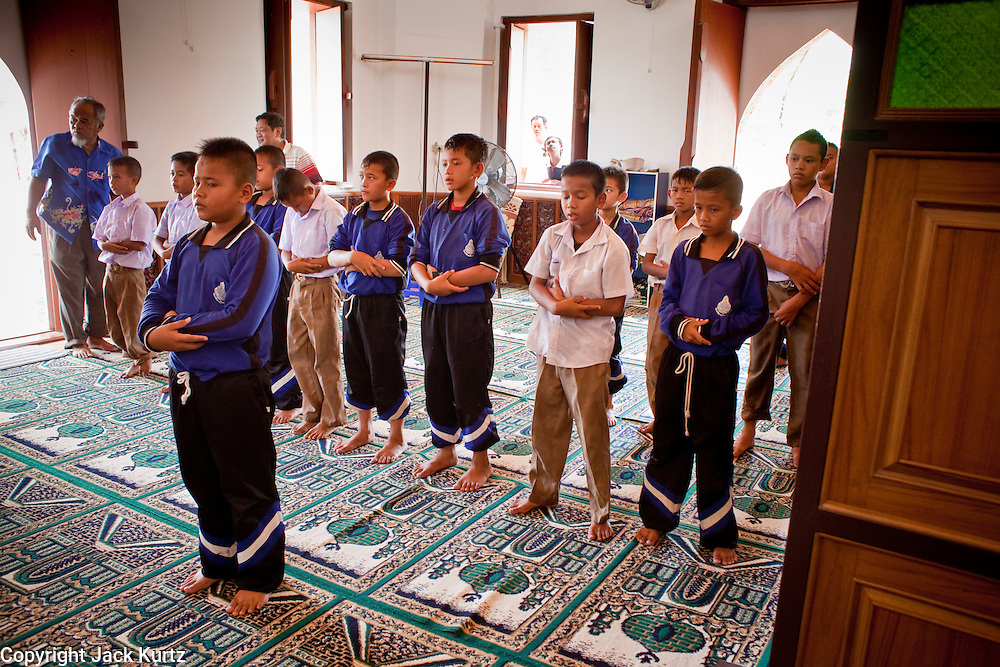 """Sept. 24, 2009 -- PATTANI, THAILAND: Thai schoolboys pray in the Krue Se Mosque in Pattani, Thailand. The Krue Se Mosque is one of Thailand's most historic mosques and long a flash point in Muslim - Buddhist confrontation. The mosque was first destroyed by advancing Thais when Pattani was an independent kingdom in 1786. It was restored in the 1980's but heavily damaged by rockets fired by unknown assailants in 2005. It has since been partially restored by local Muslims and the Thai government. Thailand's three southern most provinces; Yala, Pattani and Narathiwat are often called """"restive"""" and a decades long Muslim insurgency has gained traction recently and nearly 4,000 people have been killed since 2004. The three southern provinces are under emergency control and there are more than 60,000 Thai military, police and paramilitary militia forces trying to keep the peace battling insurgents who favor car bombs and assassination.    Photo by Jack Kurtz"""