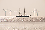 A tallship passes Crosby Beach into the Irish Sea, after leaving Liverpool on the river Mersey.