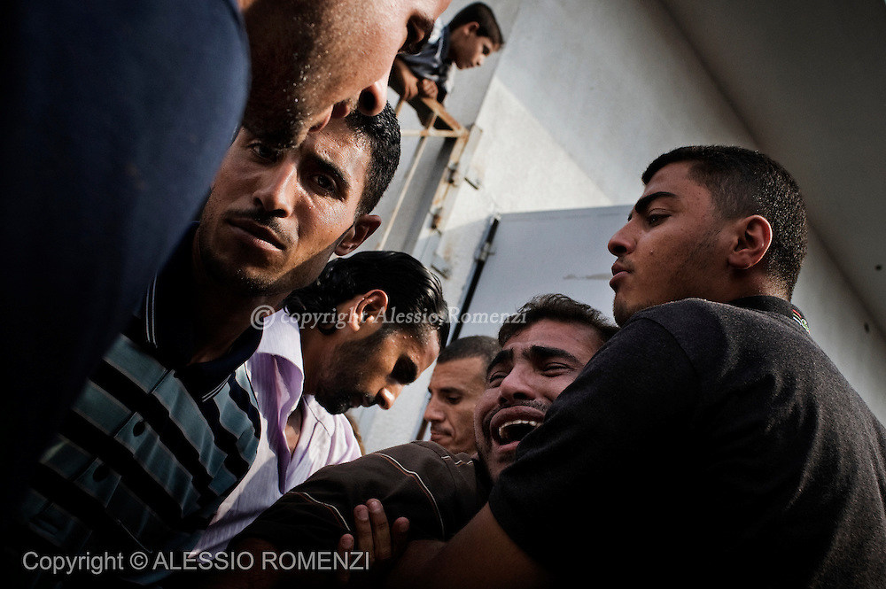 Relatives of al-Quds brigade militant Mohammed el-Kafarna mourn at the morgue of the hospital in Beit Hanun following and Israeli strike on July 21, 2010 near the border with Israel in the northern Gaza Strip, in which one person was killed and 10 others were wounded.© ALESSIO ROMENZI