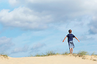 Young boy standing on sand dune in wind with arms outstretched back view