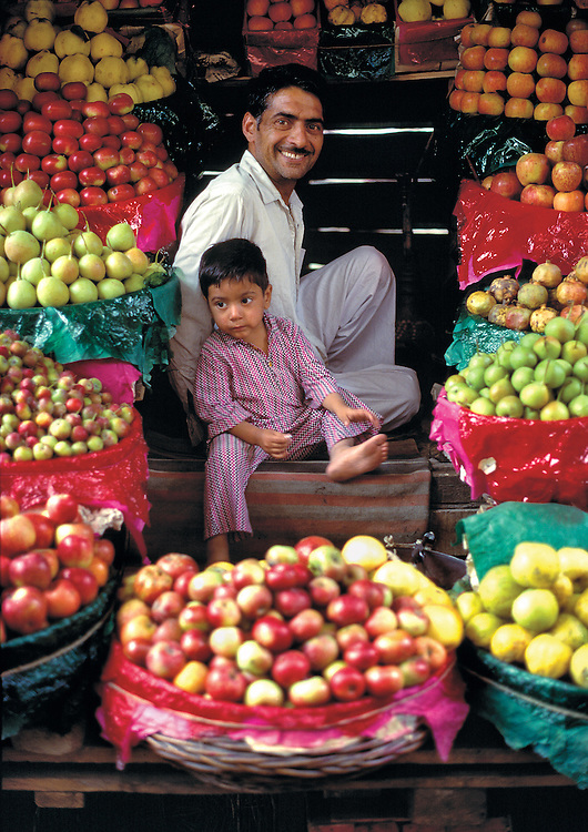 A produce merchant and his son sit among their beautiful produce, Srinagar, Kashmir, India.