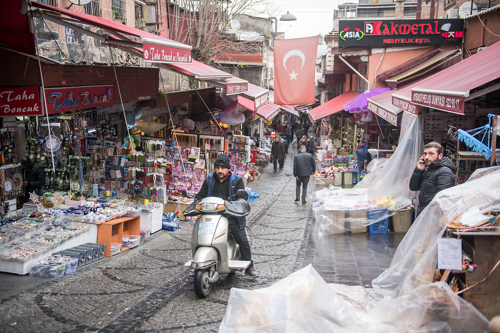 A man rides a scooter up a narrow street where shops and stalls for outdoor market line either side, Istanbul, Turkey