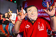 27 JULY 2013 - BANGKOK, THAILAND:  A Thai Red Shirt wearing a Thaksin Shinawatra mask, dances during the party for Thaksin Shinawatra. The Red Shirts celebrated former Prime Minister Thaksin Shinawatra's 64th birthday with a party at Phibun Prachasan School in Bangkok. They had a Buddhist Merit Making Ceremony, dinner, cake and entertainment. Most of the Red Shirt political elite traveled to Hong Kong for a party with Thaksin. Thaksin, the former Prime Minister, was deposed by a coup in 2006 and subsequently convicted of corruption related crimes. He went into exile rather than go to jail but remains very popular in rural parts of Thailand. His sister, Yingluck Shinawatra is the current Prime Minister and was elected based on her brother's recommendation.    PHOTO BY JACK KURTZ