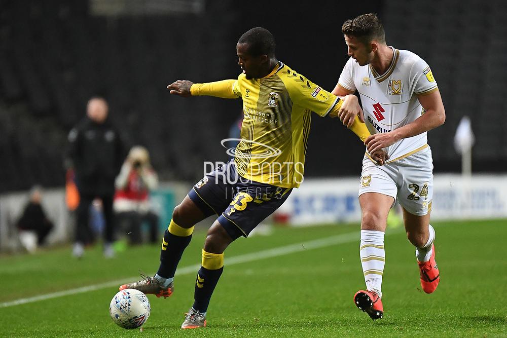 Coventry City forward Gervane Kastaneer (33) battles for possession  with Milton Keynes Dons midfielder Jordan Houghton (24) during the EFL Trophy match between Milton Keynes Dons and Coventry City at Stadium:MK, Milton Keynes, England on 3 December 2019.