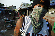 October 2004 - Phnom Penh; Cambodia - Chhin Toeun; 24; or Hawaii to his friends; walks around a central Phnom Penh market. After spending more than 7 years in prison; he was deported back to Cambodia. Previously a gang member in the US; he remains dressed like an American covered in tatoos and is seen as a foreigner to local Khmers even though he was born in Cambodia.; After escaping the Khmer Rouge regime to the US as refugees; many young American Cambodians are being sent back to Cambodia never to return to the US again. A new policy in 2002 meant that any US-Cambodian who still had not applied for US citizenship and had been convicted of a felony would be deported back to Cambodia after living in the US all their life. Over 1; 400 convicted felons are proposed to be sent back in the next few years and naturally the re-adjustment to a life they don't know or understand is a difficult one. Photo Credit: Luke Duggleby