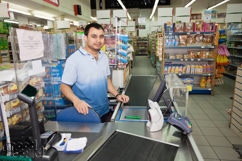 Portrait of store clerk standing at counter in supermarket