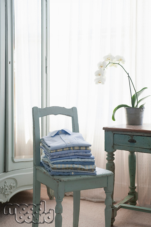 Folded shirts on  bedroom chair