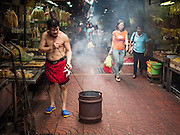 "28 AUGUST 2015 - BANGKOK, THAILAND:  A man burns paper clothes and ""ghost money"" for his  ancestors, now ghosts, on Hungry Ghost Day in Bangkok's Chinatown. Mahayana  Buddhists believe that the gates of hell are opened on the full moon of the seventh lunar month of the Chinese calendar, and the spirits of hungry ghosts allowed to roam the earth. These ghosts need food and merit to find their way back to their own. People help by offering food, paper money, candles and flowers, making merit of their own in the process. Hungry Ghost Day is observed in communities with a large ethnic Chinese population, like Bangkok's Chinatown.      PHOTO BY JACK KURTZ"
