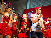 27 JULY 2013 - BANGKOK, THAILAND:  Entertainers, including Thai women in Las Vegas style outfits, put on show for Thai Red Shirts at a birthday for Thaksin Shinawatra. The Red Shirts celebrated former Prime Minister Thaksin Shinawatra's 64th birthday with a party at Phibun Prachasan School in Bangkok. They had a Buddhist Merit Making Ceremony, dinner, cake and entertainment. Most of the Red Shirt political elite traveled to Hong Kong for a party with Thaksin. Thaksin, the former Prime Minister, was deposed by a coup in 2006 and subsequently convicted of corruption related crimes. He went into exile rather than go to jail but remains very popular in rural parts of Thailand. His sister, Yingluck Shinawatra is the current Prime Minister and was elected based on her brother's recommendation.    PHOTO BY JACK KURTZ