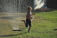 Spencer Norris runs through a sprinkler to cool off  in Oxford, Miss. on Tuesday, July 2, 2012.