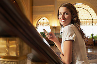 Woman leaning on railing holding mobile phone portrait.