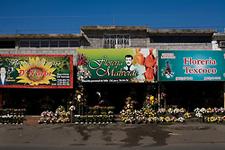 A shop named after Jesus Malverde sells flowers near the cematary in Culiacan, Mexico.  Malverde is a folk saint worshipped by many people in the underworld and often associated with narcoculture and drug dealers. He is thought of as the Mexican version of Robin Hood, looking after those who have been forgotten by the Church and involved in ilicit activities.