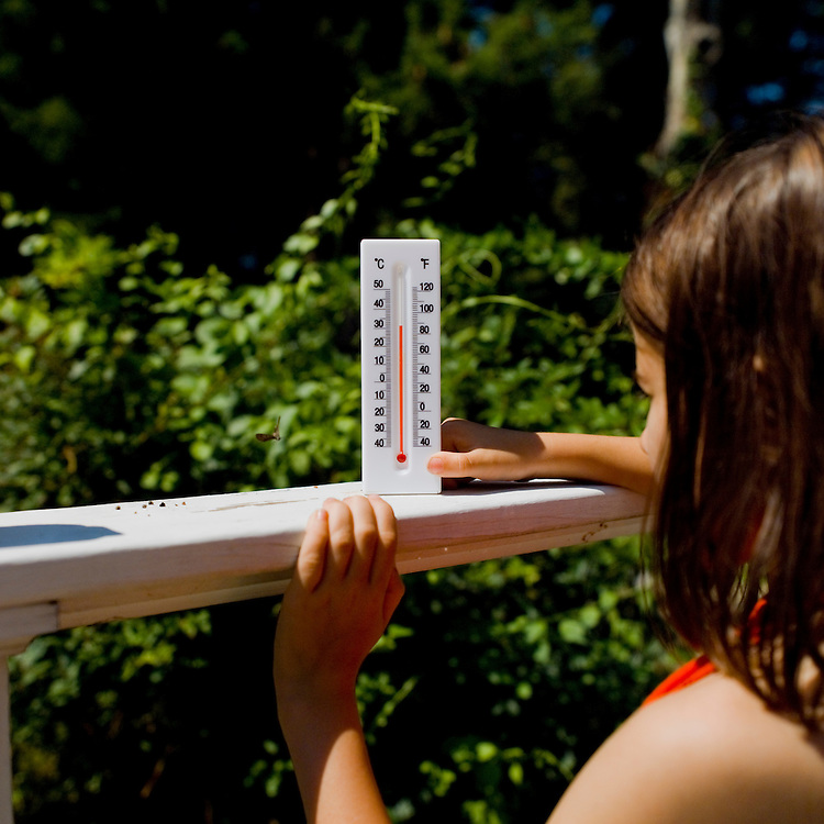 Girl using thermometer to measure outdoor temperature.