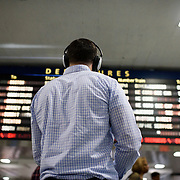 May 24, 2016 - New York, NY :  A commuter wearing over-ear headphones waits under the departures board in the Amtrak Concourse on Penn Station's upper level, for his trains to be assigned a track during the evening rush on Tuesday. Above him, music filters into the space through a series of in-ceiling speakers. CREDIT: Karsten Moran for The New York Times