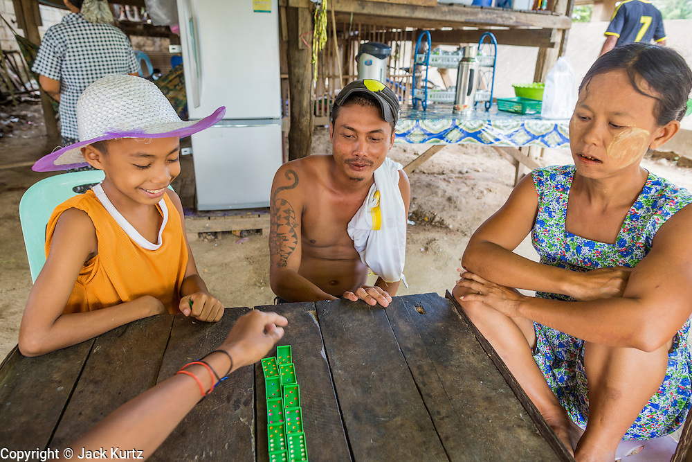 23 MAY 2013 - MAE SOT, TAK, THAILAND: Burmese migrants living in Thailand play dominoes in a Burmese tea house in Mae Sot, Thailand. Fifty years of political turmoil in Burma (Myanmar) has led millions of Burmese to leave their country. Many have settled in neighboring Thailand. Mae Sot, on the Mae Nam Moei (Moei River) is the center of the Burmese emigre community in central western Thailand. There are hundreds of thousands of Burmese refugees and migrants in the area. Many live a shadowy existence without papers and without recourse if they cross Thai authorities. The Burmese have their own schools and hospitals (with funding provided by NGOs). Burmese restaurants and tea houses are common in the area.     PHOTO BY JACK KURTZ