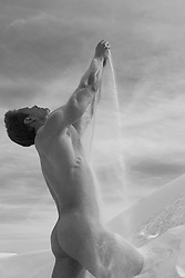 naked man pouring sand down his naked body