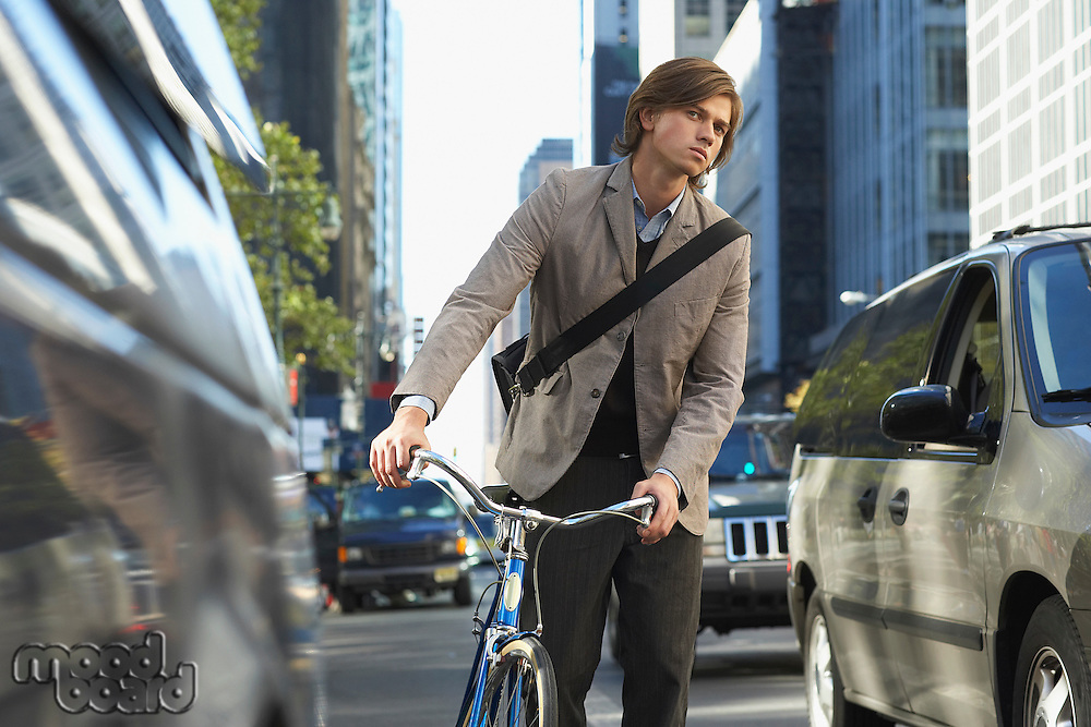 Man standing by bicycle on busy street