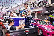 "13 APRIL 2013 - BANGKOK, THAILAND:  Thais use a pickup truck to get through a water fight on Khao San Road, which is Bangkok's ""backpacker"" district, during Songkran celebrations in the Thai capital. Songkran is celebrated in Thailand as the traditional New Year's Day from 13 to 16 April. The date of the festival was originally set by astrological calculation, but it is now fixed. If the days fall on a weekend, the missed days are taken on the weekdays immediately following. Songkran is in the hottest time of the year in Thailand, at the end of the dry season and provides an excuse for people to cool off in friendly water fights that take place throughout the country. Songkran has been a national holiday since 1940, when Thailand moved the first day of the year to January 1.   PHOTO BY JACK KURTZ"