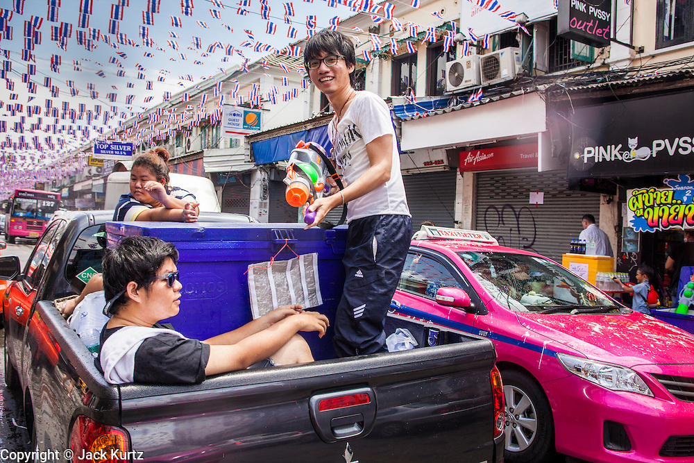 """13 APRIL 2013 - BANGKOK, THAILAND:  Thais use a pickup truck to get through a water fight on Khao San Road, which is Bangkok's """"backpacker"""" district, during Songkran celebrations in the Thai capital. Songkran is celebrated in Thailand as the traditional New Year's Day from 13 to 16 April. The date of the festival was originally set by astrological calculation, but it is now fixed. If the days fall on a weekend, the missed days are taken on the weekdays immediately following. Songkran is in the hottest time of the year in Thailand, at the end of the dry season and provides an excuse for people to cool off in friendly water fights that take place throughout the country. Songkran has been a national holiday since 1940, when Thailand moved the first day of the year to January 1.   PHOTO BY JACK KURTZ"""
