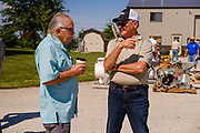 "06 AUGUST 2020 - FAIRFIELD, IOWA: GARY ADAM, right, talks to a bidder before the auction on his farm near Fairfield. Adam, 72 years old, has been farming in the Fairfield area since 1971. He decided to retire this year because he wants to travel and because it's so difficult to make money in farming this year. He said he wants to ""shed the risk and responsibility. If things were super good, like they were 2006-2012, I might stay in it, but they're not."" An increasing number of farmers in the Midwest are retiring this year as it becomes harder to make money on crops. In addition to low prices, Iowa farmers are being hit with a drought this year, with well below average rain over most of the state. Because of the COVID-19 pandemic, the auction on Adam's farm was one of the first live in person auctions since winter. Most auctions are now done on line.    PHOTO BY JACK KURTZ"
