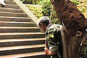 China, Sichuan Province, Mount Emei Wannian Temple porter carrying large stone carved brick up the steps
