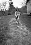 woman cycling over a path behind the house rural France 1950s