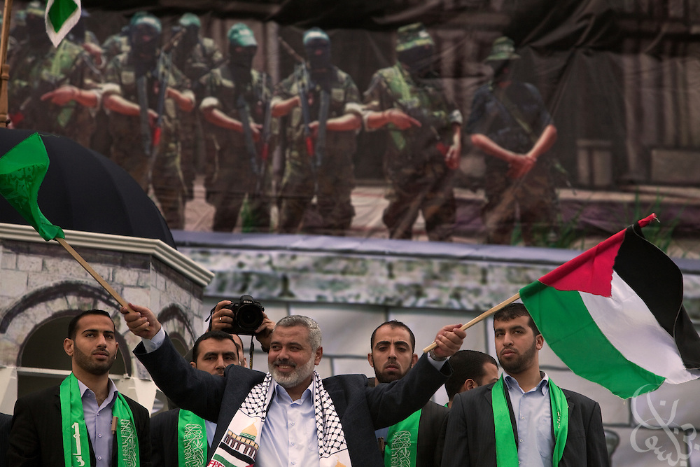 "De facto Palestinian Prime Minister Ismail Haniyeh waves both HAMAS and Palestinian flags during a December 14,2009 rally to commemorate the 22nd anniversary of HAMAS in Gaza City, Gaza. ""Those who planned the war and executed it did not expect these crowds to come today waving their flags ... Hamas did not collapse after the war; the enemy leaders collapsed,"" he said."