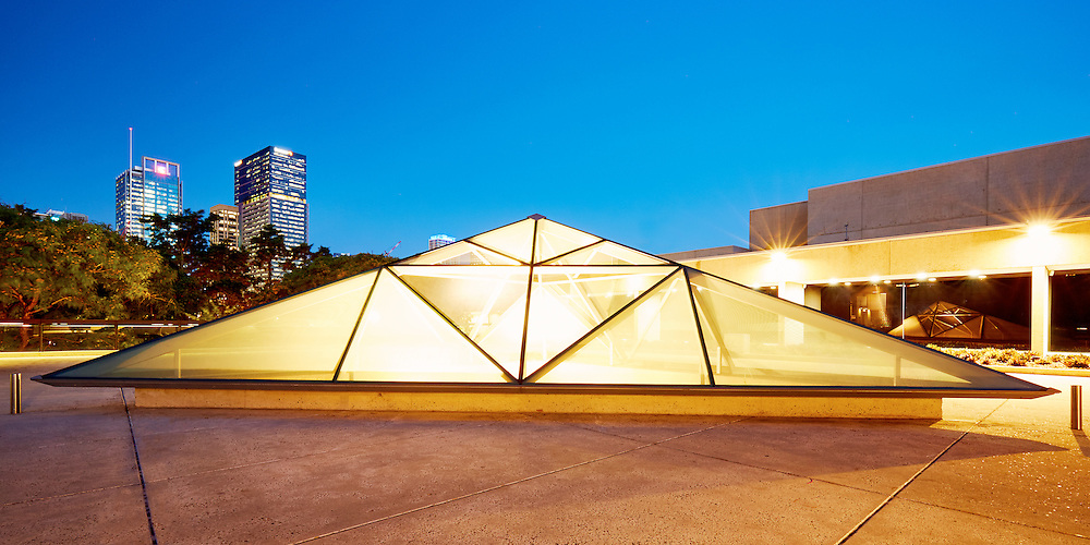 The Queensland Museum pyramid skylight lights up at dusk in Brisbane.