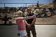 Ms. Lily Sarosi shooting under the assistance of the instructor Eitan Cohen. During the training the whole family shots with rifles and guns.