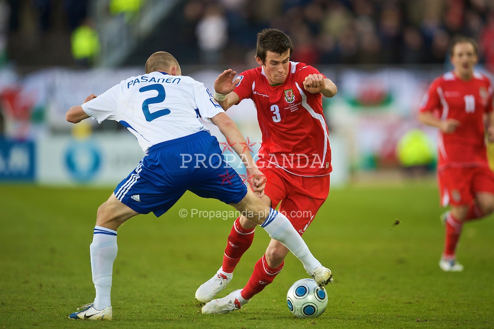 HELSINKI, FINLAND - Saturday, October 10, 2009: Wales' Gareth Bale and Finland's Petri Pasanen during the 2010 FIFA World Cup Qualifying Group 4 match at the Olympic Stadium. (Pic by David Rawcliffe/Propaganda)