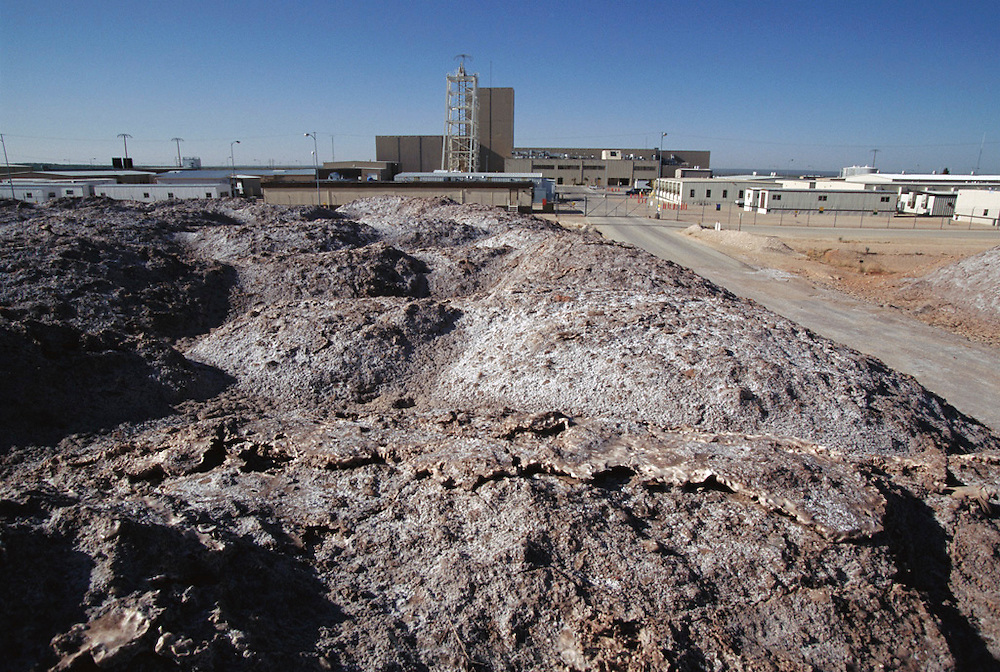 Salt tailing pile in foreground of an above ground view of underground storage of radioactive wastes for the Waste Isolation Pilot Project (WIPP), 700 meters below ground. WIPP is a research project to determine the suitability of the local salt rocks as a storage site for highly- radioactive transuranic waste from atomic power stations. Such waste materials may have radioactive half-lives of thousands of years, and so must be isolated in a geologically stable environment. On the left is an experiment testing the design of containers carrying vitrified waste. The mine is located near Carlsbad, New Mexico, USA. (1998)