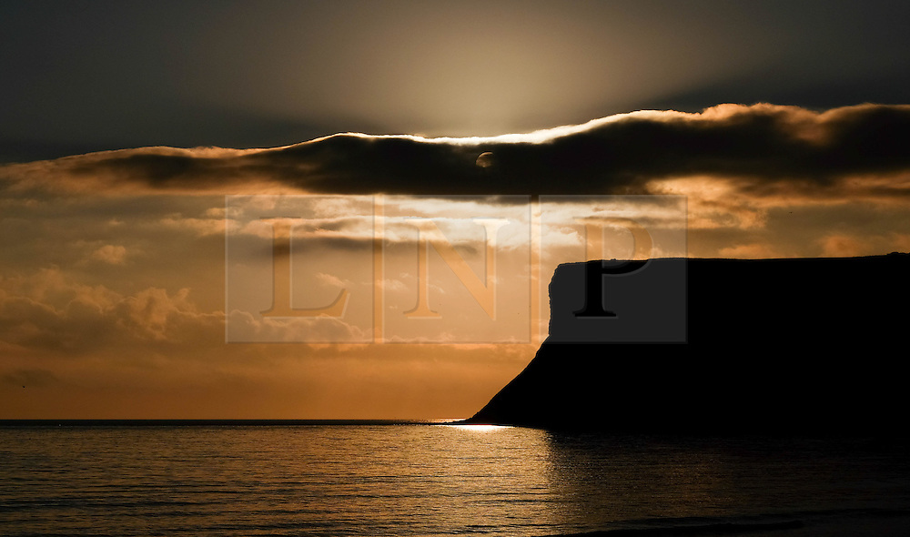 © Licensed to London News Pictures. <br /> 18/08/2016. <br /> Satburn-By-The-Sea, UK.  <br /> <br /> The sun is partially hidden by clouds as it rises over cliffs at Saltburn-By-The-Sea.<br /> <br /> Photo credit: Ian Forsyth/LNP